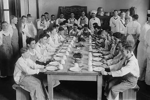 Naval Cadets sit at long table with bowls in front