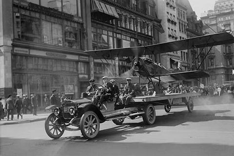Biplane with spinning propeller is towed down Fifth Avenue New York for July 4th Parade