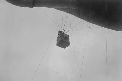 Military Observer hangs from a Balloon by guide wires looking over battlefield