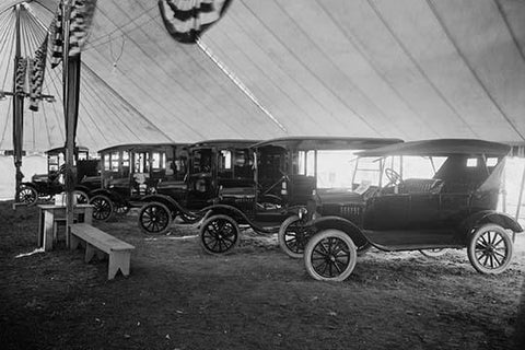 Automobiles on Display in Tent Under American Flag Banners