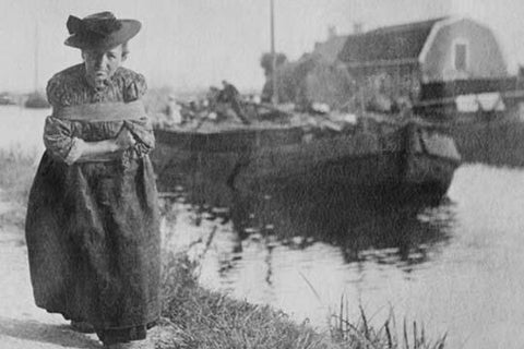 A Older Dutch woman has a bustle around her chest as she pulls a barge down a canal.