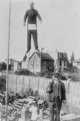 An old man carrying a rifle guards a hanging effigy of Kaiser Wilhelm