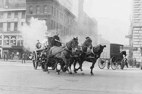 A Team of Horses pulls a steam pumper across paved streets toward a fire scene.