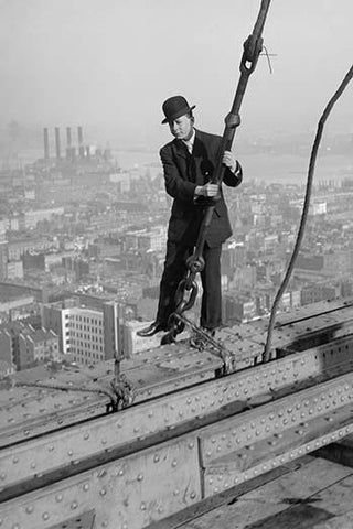 Cameraman in suit holds onto cable as he walks unharnessed over a skyscraper's steel girders