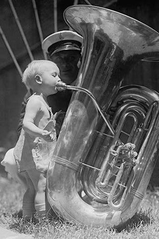 An nearly naked infant toots a tuba many times his size