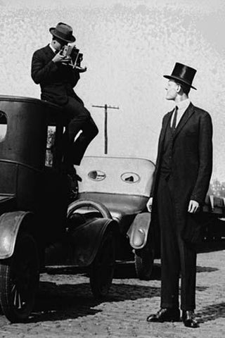 Photographer Mounts himself on the roof of a car to shoot a pictures of an exceedingly tall men in a top hat.
