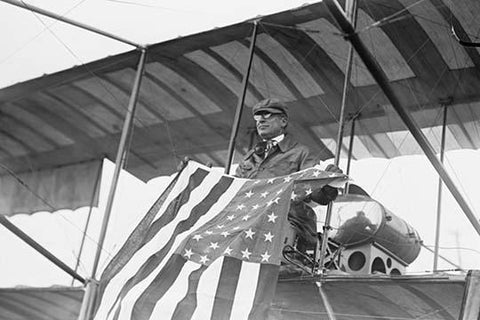 Aviator C.B. Harmon Unfurls Stars and Stripes from his pilot seat on his Biplane.