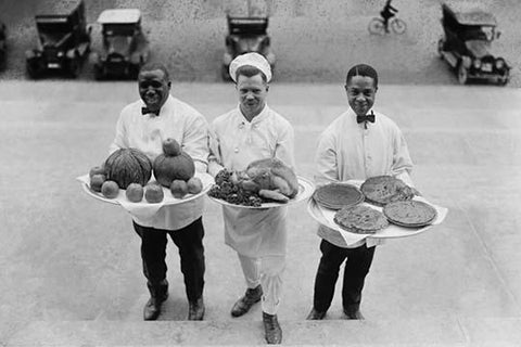 Three Chefs stand on bottom of a line of steps and hold up Thanksgiving platters of Pies, apples and a Turkey
