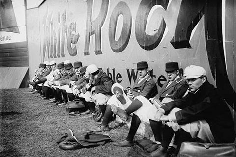 Philadelphia Americans Relax by sitting along the Center Field Fence at the Park