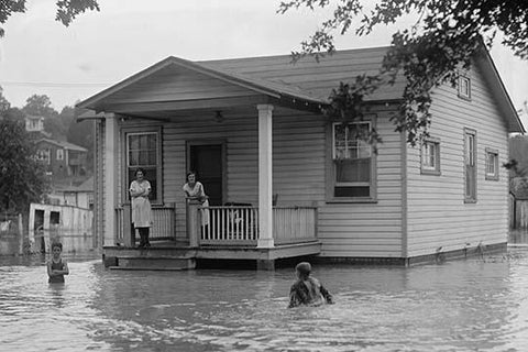 Children on porch of house surrounded by flood