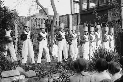 Line of Boys pose as Soldiers with inverted pails on their heads