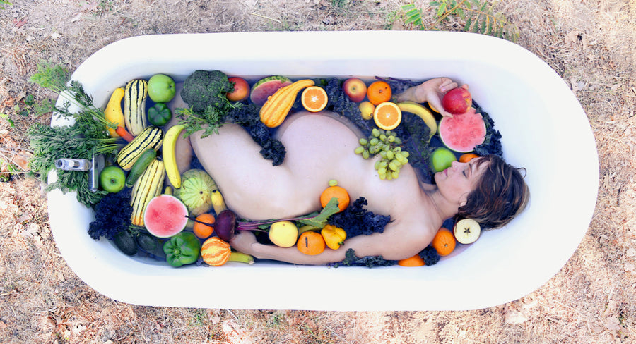 Giving birth can be messy, with postpartum blues and too much laundry. But a woman's body is divine. Luscious, fertile and deserving of support. Pregnant woman in a bathtub filled with fruits and vegetables.