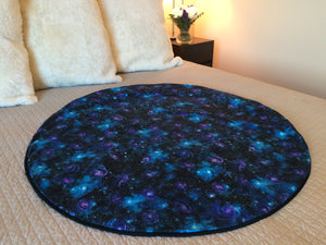 The Galaxy Gazing Venus Mat is a swirl of purple and blue solar systems on a black background studded with stars.