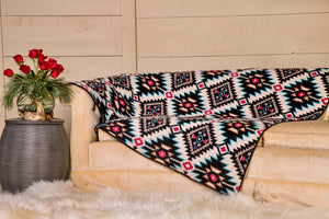 The Water is Life fleece Venus Mat is covered with a bold red black and blue geometric pattern and a sky blue backing.