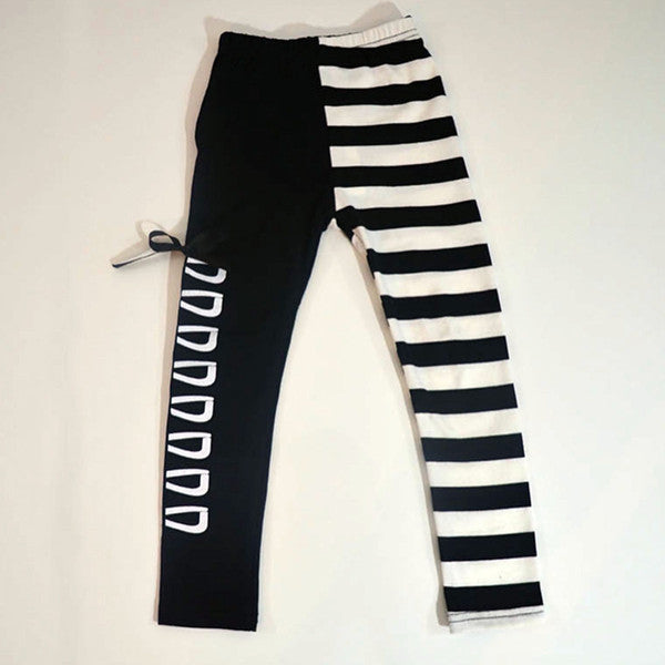 Trendy black and white children's leggings with one lace up leg and one striped leg.