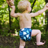 Small white child faces away from the camera, holding hands with two larger people and walking through the forest wearing only an AMP cloth diaper