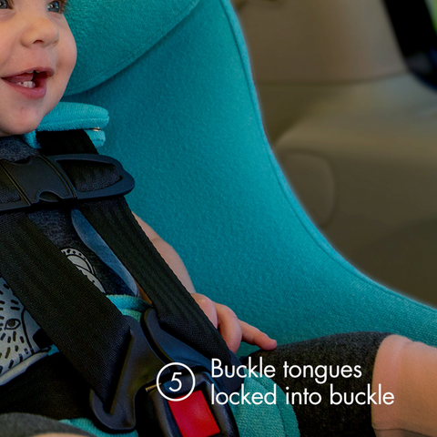 "Young toddler in a blue clek car seat with text ""buckle tongues locked into buckle"""