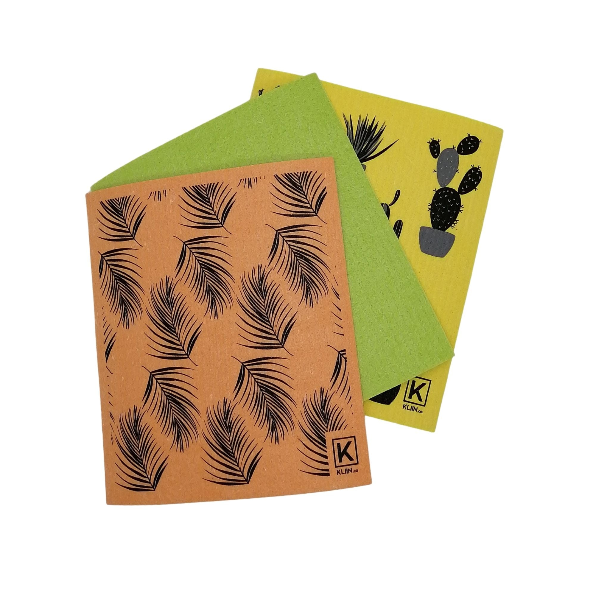 kliin reusable paper towel foliage set laid out yellow towel with potted plant graphic, solid lime green towel, and light orange towel with leaf graphic