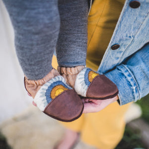 nooks design canvas and leather booties in baffin (dark brown, tan, white, blue, orange, yellow) on a small child's feet, held by an adult