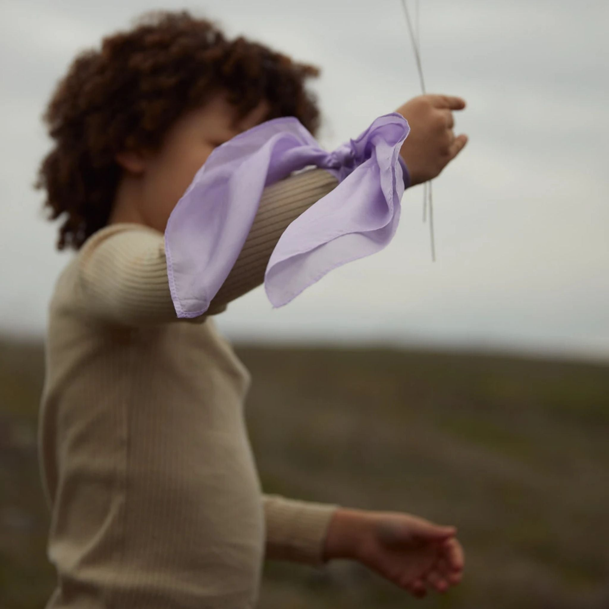 sarah's silks mini playsilks lavender tied on wrist of young child with medium brown skin and dark brown curly hair