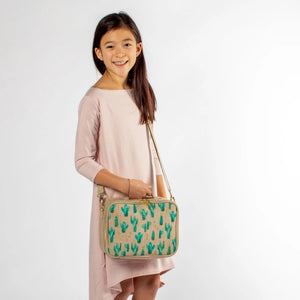 so young lunch bag cacti desert, tan and gold trim and handles, gold and green cactus print worn around the shoulder of a medium skin tone smiling kid