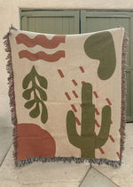Woven Blanket with an abstract desert design in warm red and green tones