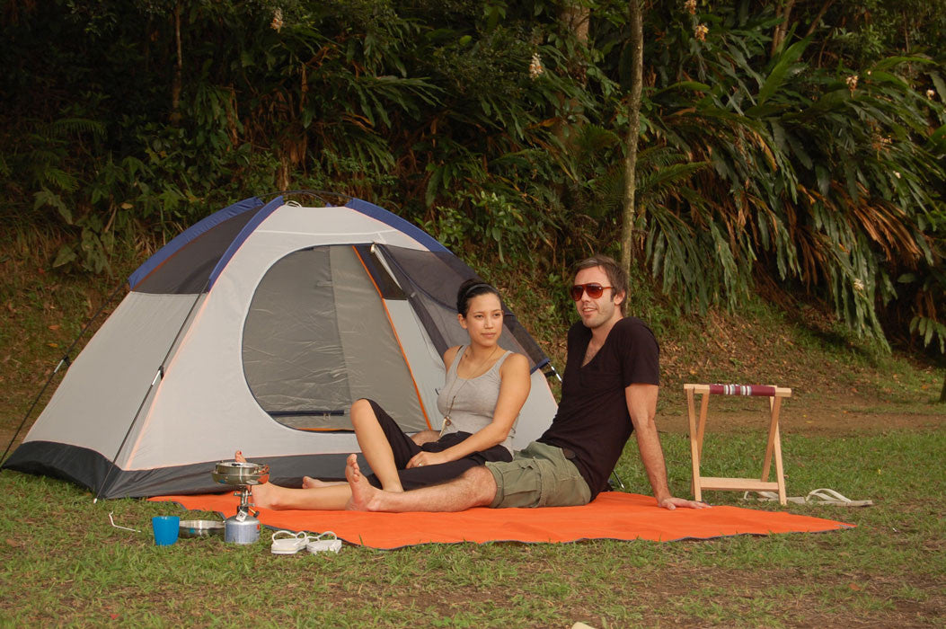 Couple Camping sitting on orange Sand-Free mat