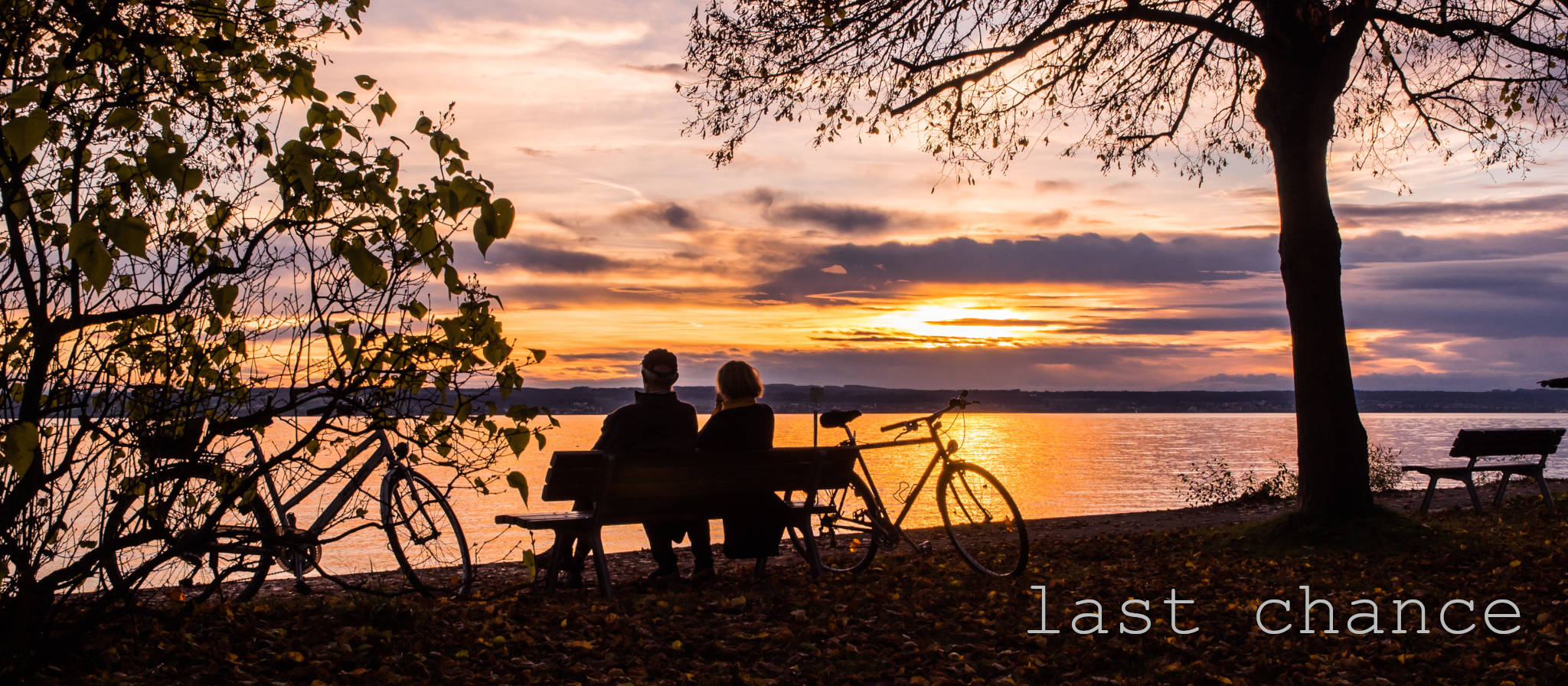 Upside Cyclestyle's Last Chance collection - man & woman with bicycles at lake during sunset