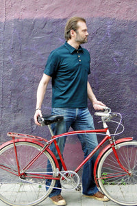 Upside Cyclestyle Men's Polo Shirt in Teal on model with bicycle