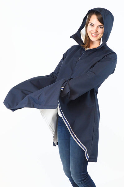 Upside Cyclestyle Women's Godet Coat in Navy Blue on model in cycling position for weather protection