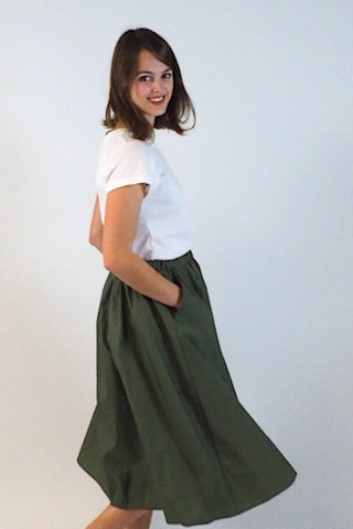 Upside Cyclestyle Women's Nylon Skirt with Snap in Olive on model with hands in pocket