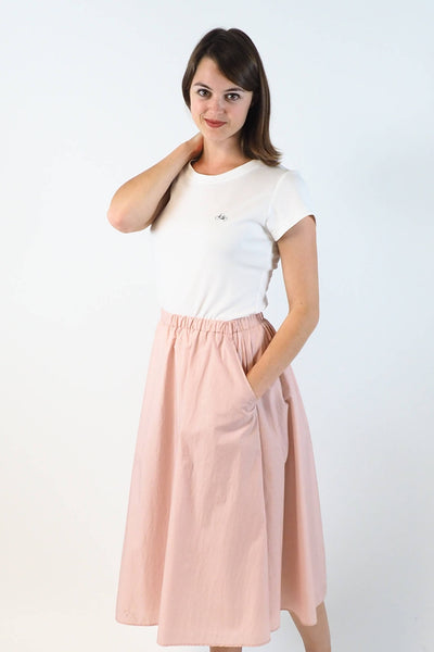 Upside Cyclestyle Women's Nylon Skirt with Snap in Pink on model with hand in pocket