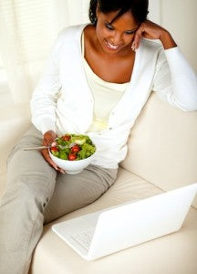 Adult black woman eating healthy green salad