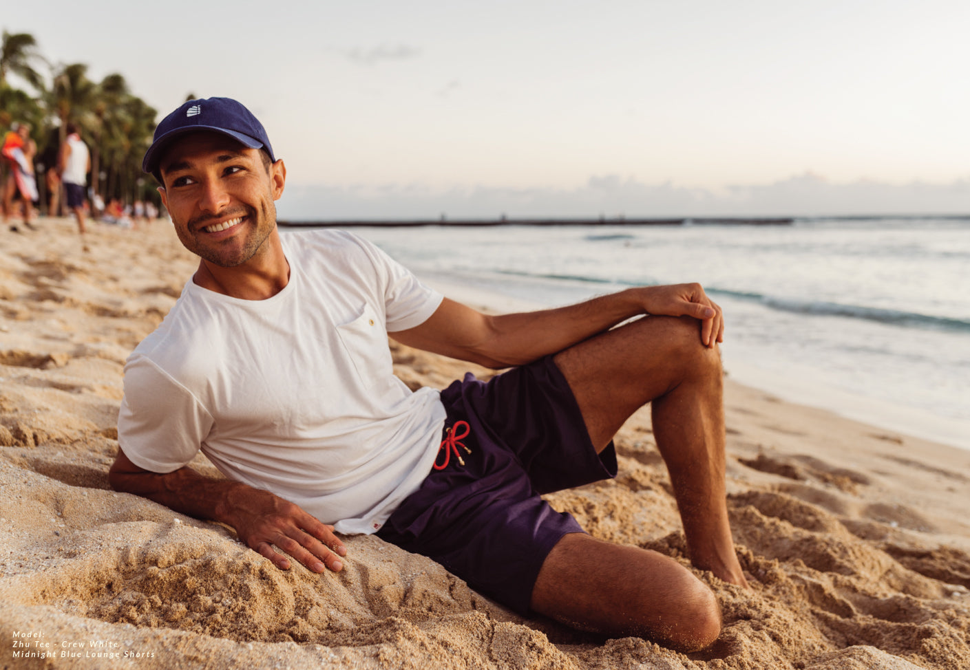 Relaxing on the beach with White bamboo t-shirt and Mighnight blue lounge shorts with tanbark sail cap navy