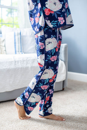 Dolphin hem pajama pants with elastic waistline and navy trim. Cream, red, and pink floral pattern. Match with big sister, big brother, Dad, and newborn.