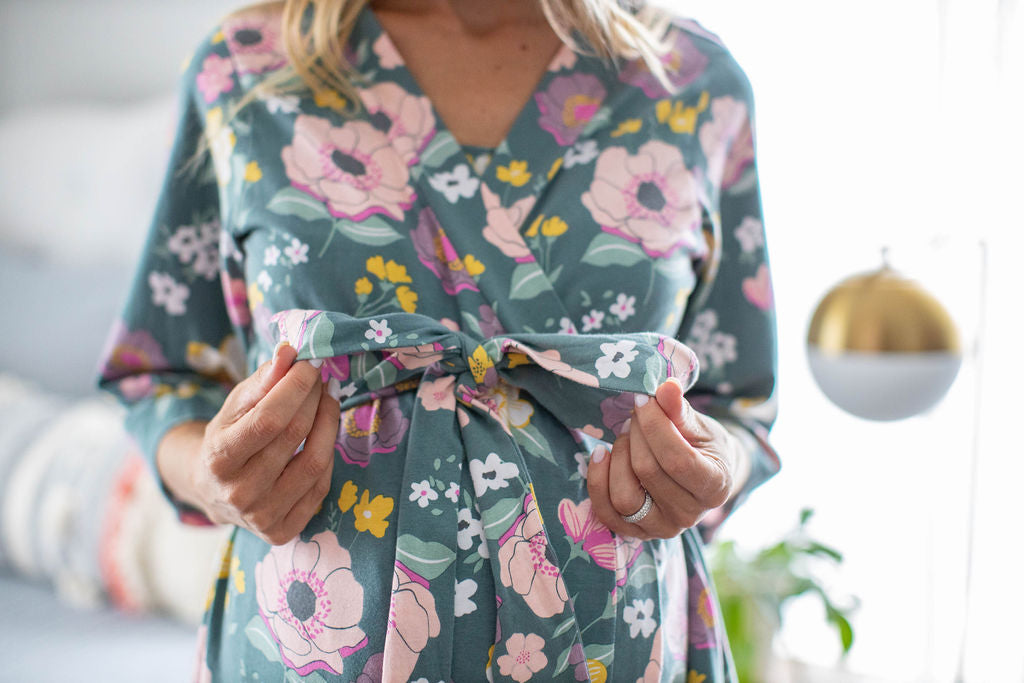 Charlotte maternity robe with pockets, belt closure, and knee length. Pink and yellow flowers against green background.