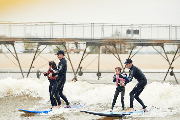 Two AWOW volunteers surfing with two kids.