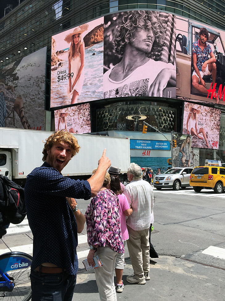 Clay pointing at his billboard in Times Square