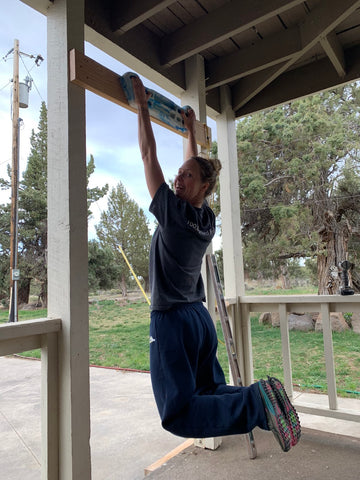 Jessica on a hangboard at home to improve upper body strength