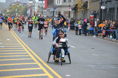 The Kyle Pease Foundation volunteer pushing an assisted athlete during a marathon