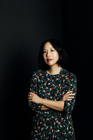 Jen Sookfong Lee standing with arms crossed and a dark background
