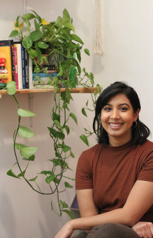 Pia Singhal sitting beside a shelf of books and a plant