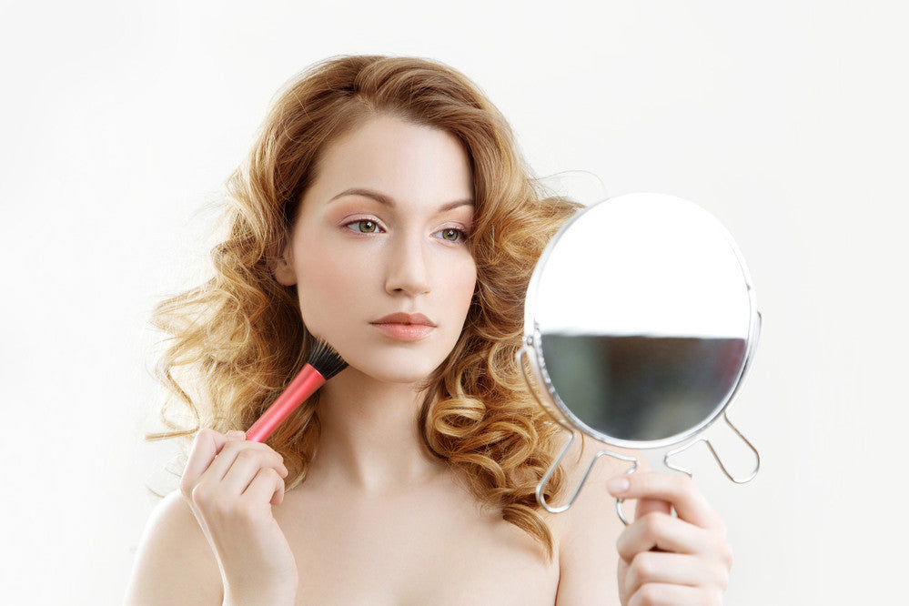 A young woman looking into the mirror while applying makeup