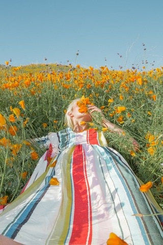 Girl in a rainbow striped dress lying in a meadow looking at the sky