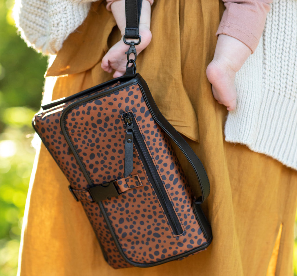 woman holds baby and dockatot leopard print clutch changing bag