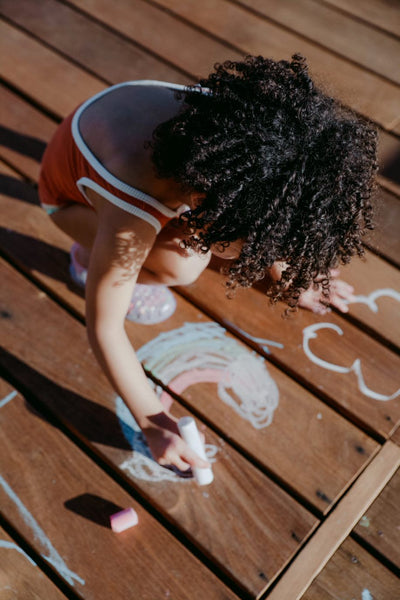 Little Girl drawing with chalk on wooden decking