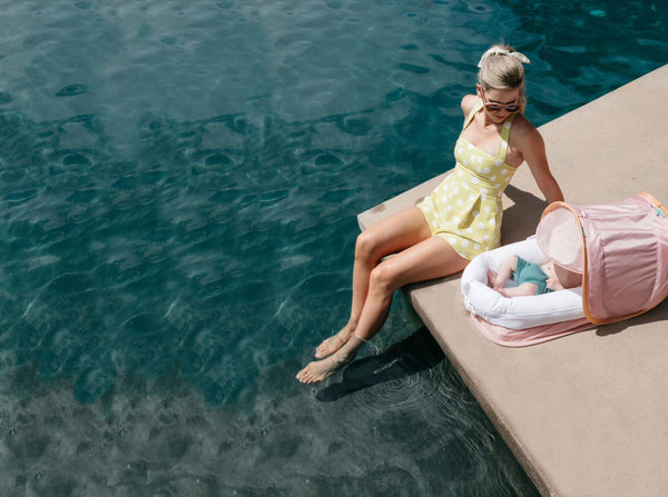 Woman dipping her toes into a pool with a baby lounging in a DockATot Deluxe+ dock with Cabana Kit