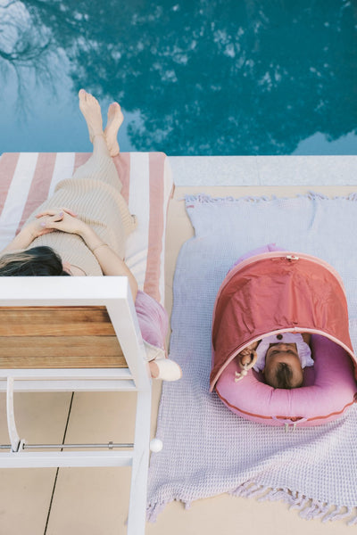 woman resting on a sun lounger whilst her baby is lounging in a DockATot Deluxe+ dock with Cabana Kit