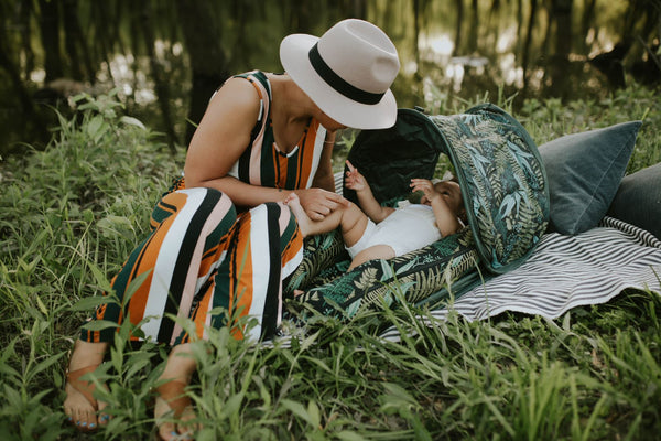 woman sitting in a grassy woodland with her baby lounging in a DockATot Deluxe+ with Cabana Kit