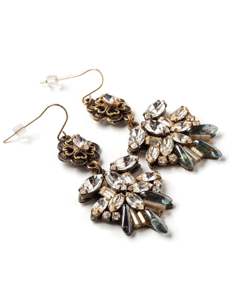 Three quarter closeup view of a pair of ornate statement earrings with rhinestone navettes and floral tops
